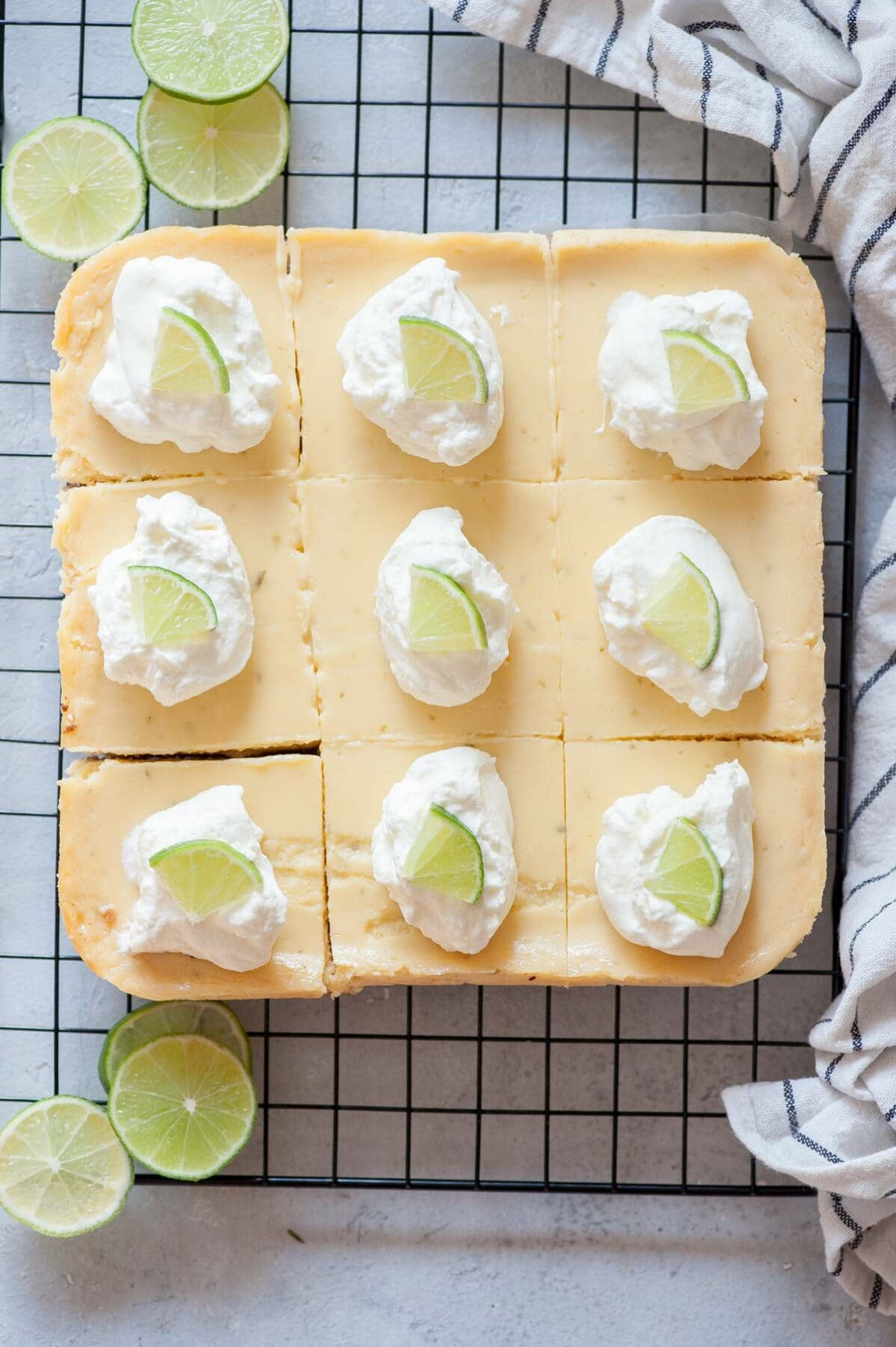 Key lime pie bars topped with whipped cream and lime slices on a black cooking rack.