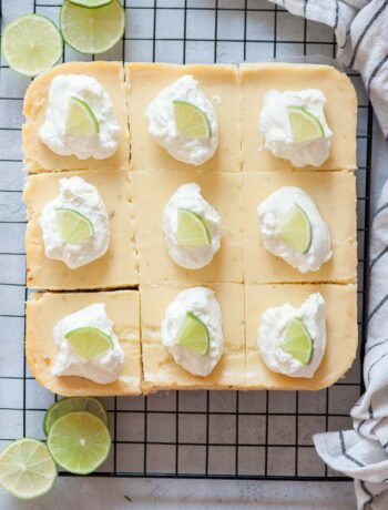 Key lime pie bars topped with whipped cream and lime slices on a cooling rack.