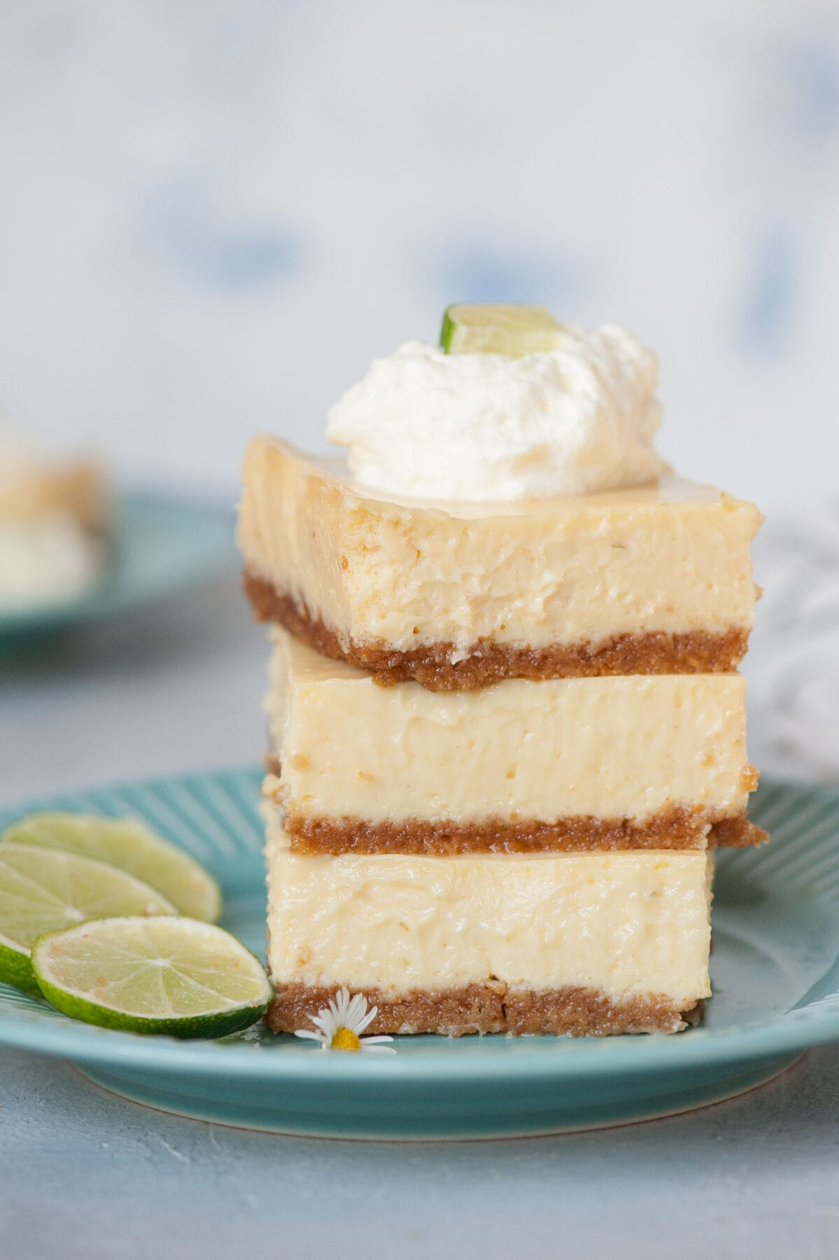 A stack of Key lime pie bars topped with whipped cream on a blue plate.
