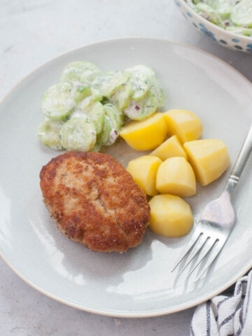 Ground pork patties, potatoes, and cucumber salad on a blue plate.