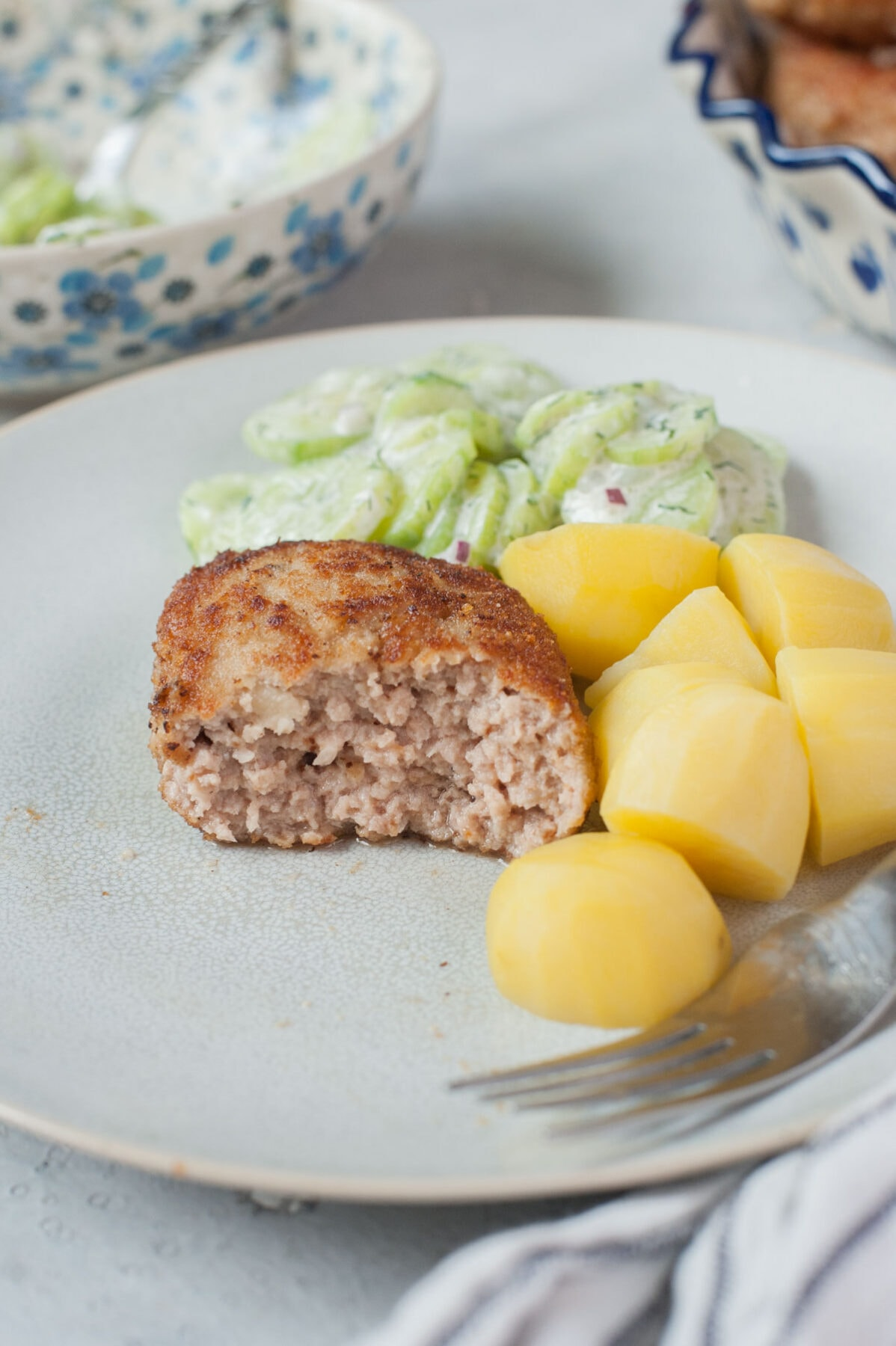 Kotlety mielone (Polish meat patties) on a blue plate with potatoes and cucumber salad.