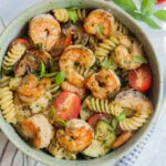 Shrimp pesto pasta in a green bowl.
