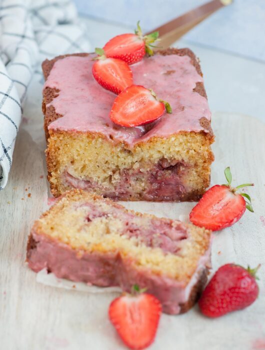 Strawberry bread with a slice cut off on a beige wooden board topped with strawberries.