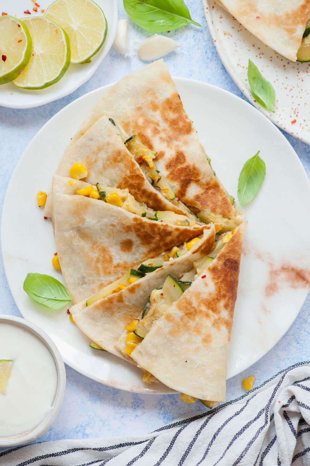 Zucchini quesadilla triangles on a white plate.