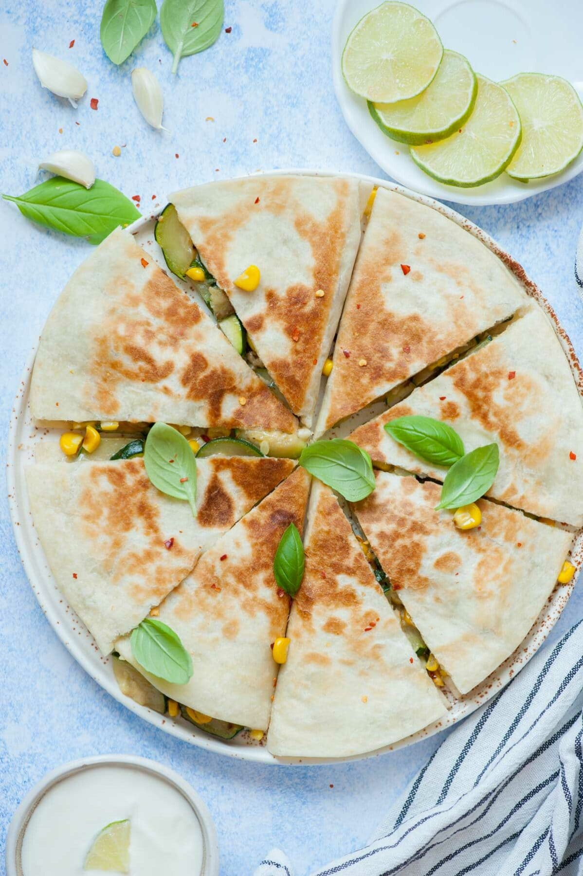 Zucchini quesadillas cut into triangles on a white plate, topped with basil leaves.