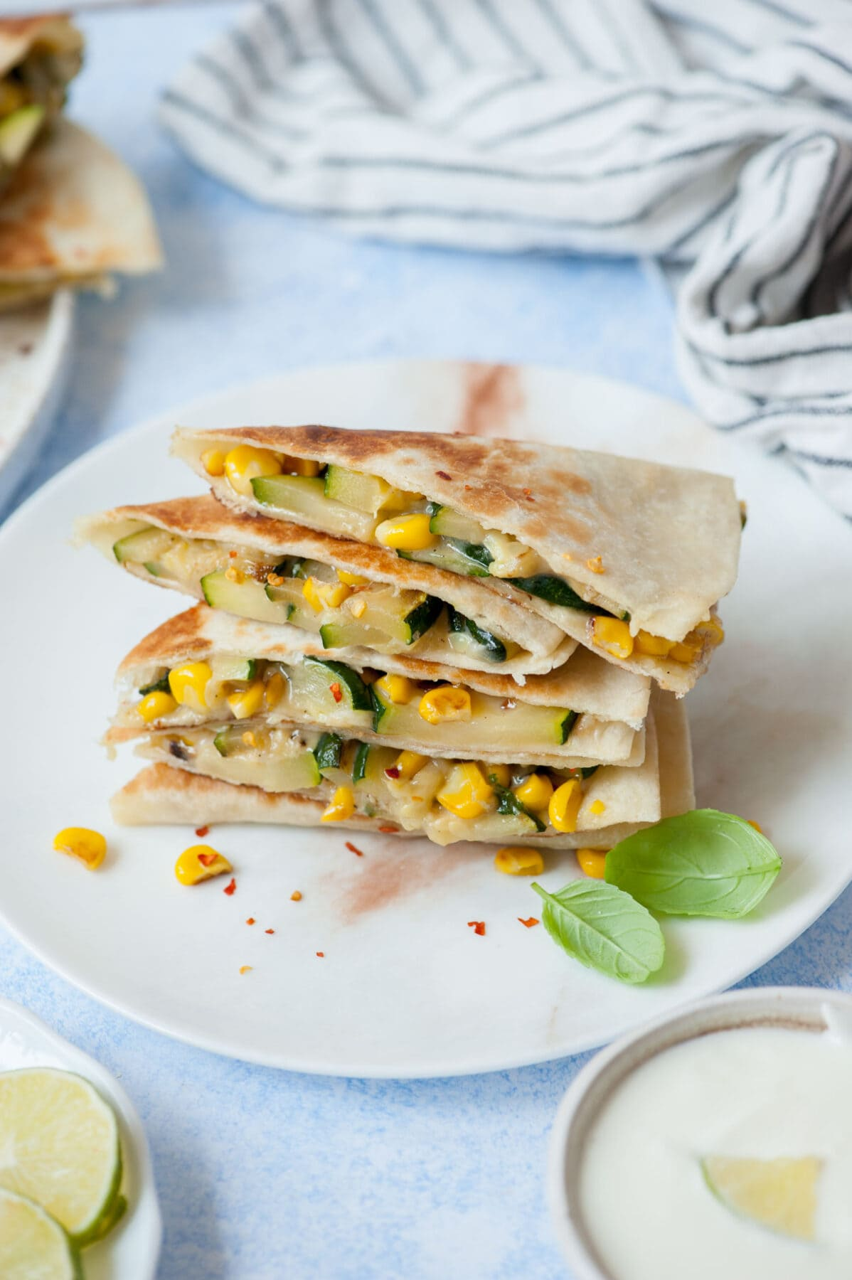 A stack of zucchini quesadilla on a white plate.