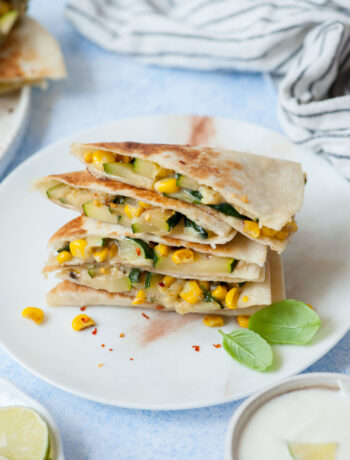 A stack of zucchini quesadillas on a white plate.