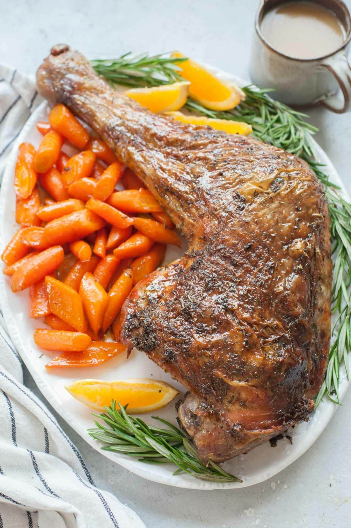 Whole baked turkey leg on a white plate with glazed carrots, rosemary springs and orange wedges.