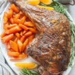 Whole roasted turkey leg on a white plate served with glazed carrots and potatoes.