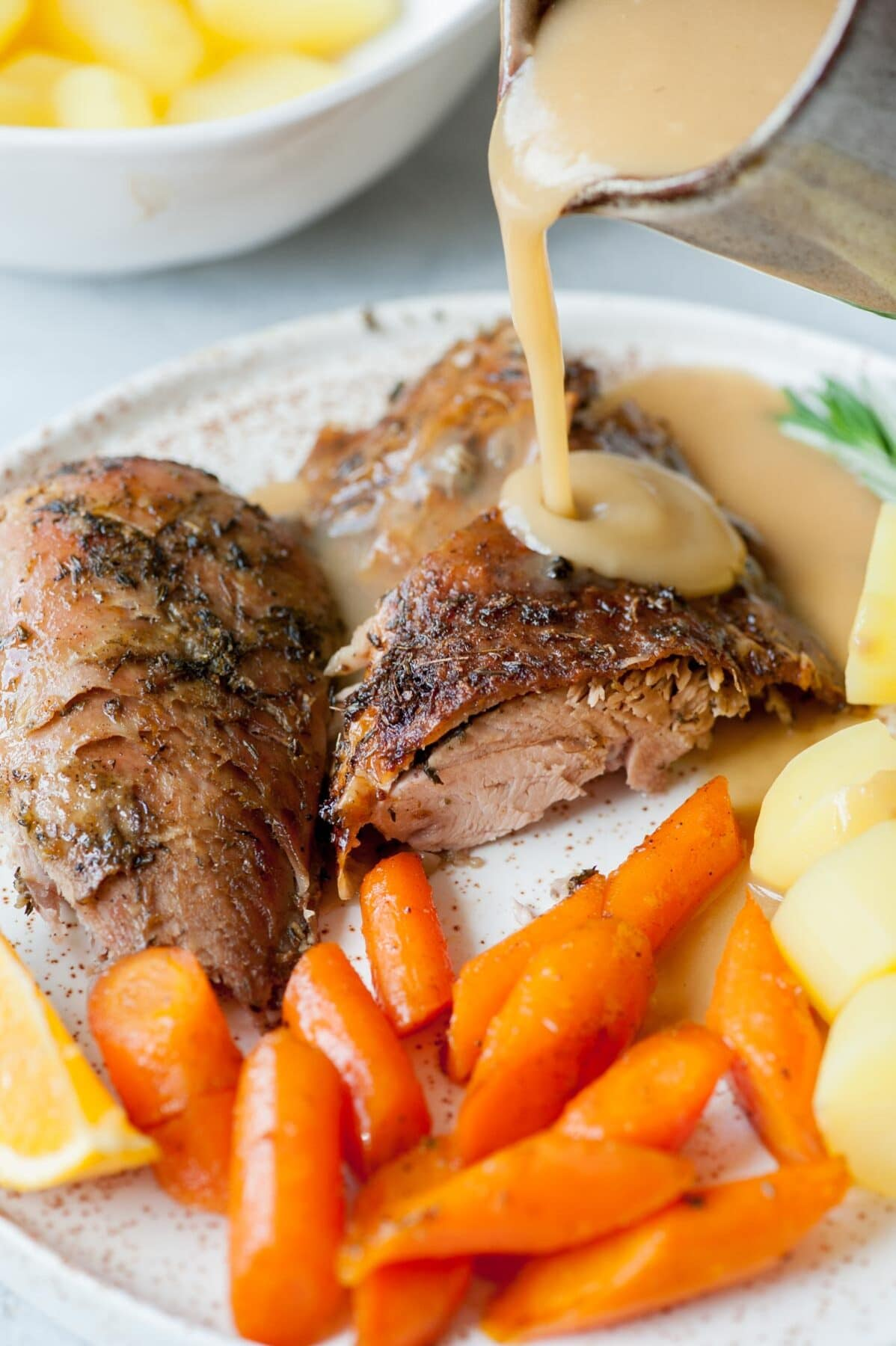 Gravy is being poured over baked turkey leg on a white plate with glazed carrots and potatoes.