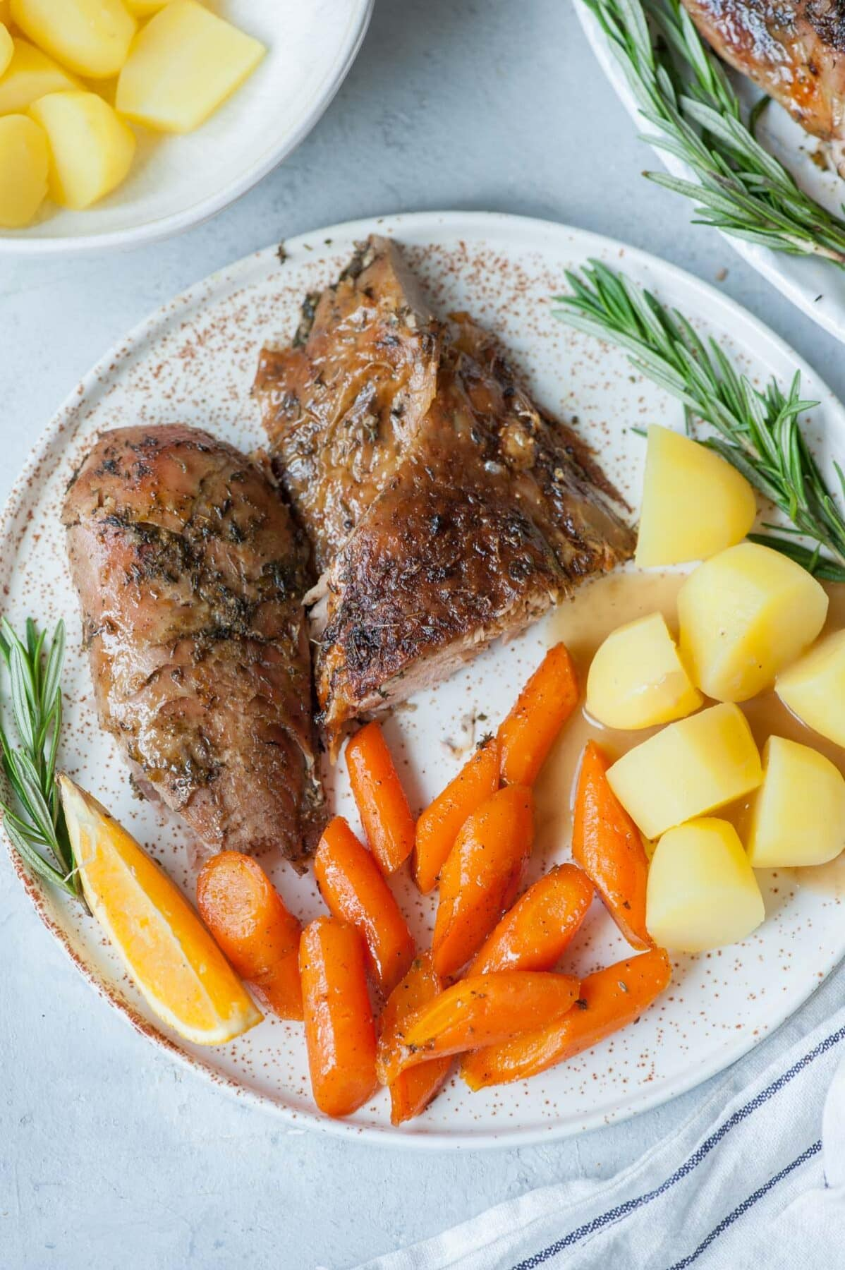 Roasted turkey leg on a white plate with glazed carrots, potatoes and gravy.