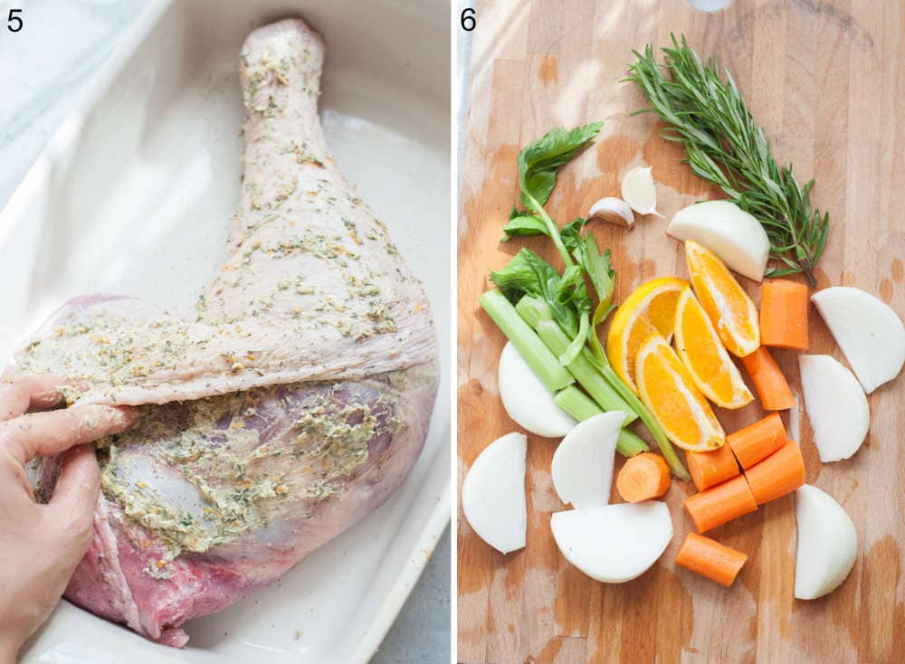 Turkey leg is being spread with herb butter. Chopped vegetables and herbs on a wooden board.