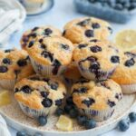 Blueberry muffins on a white plate. Blueberries and lemon slices scattered around.