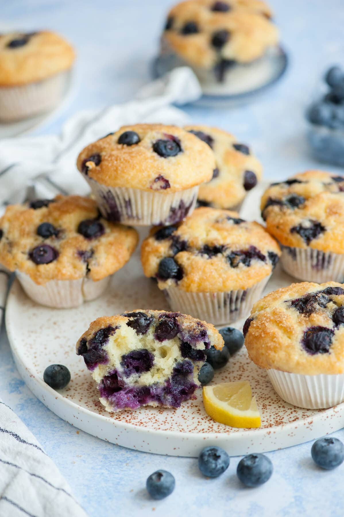 Blueberry yogurt muffins on a white plate with one muffin cut in half.