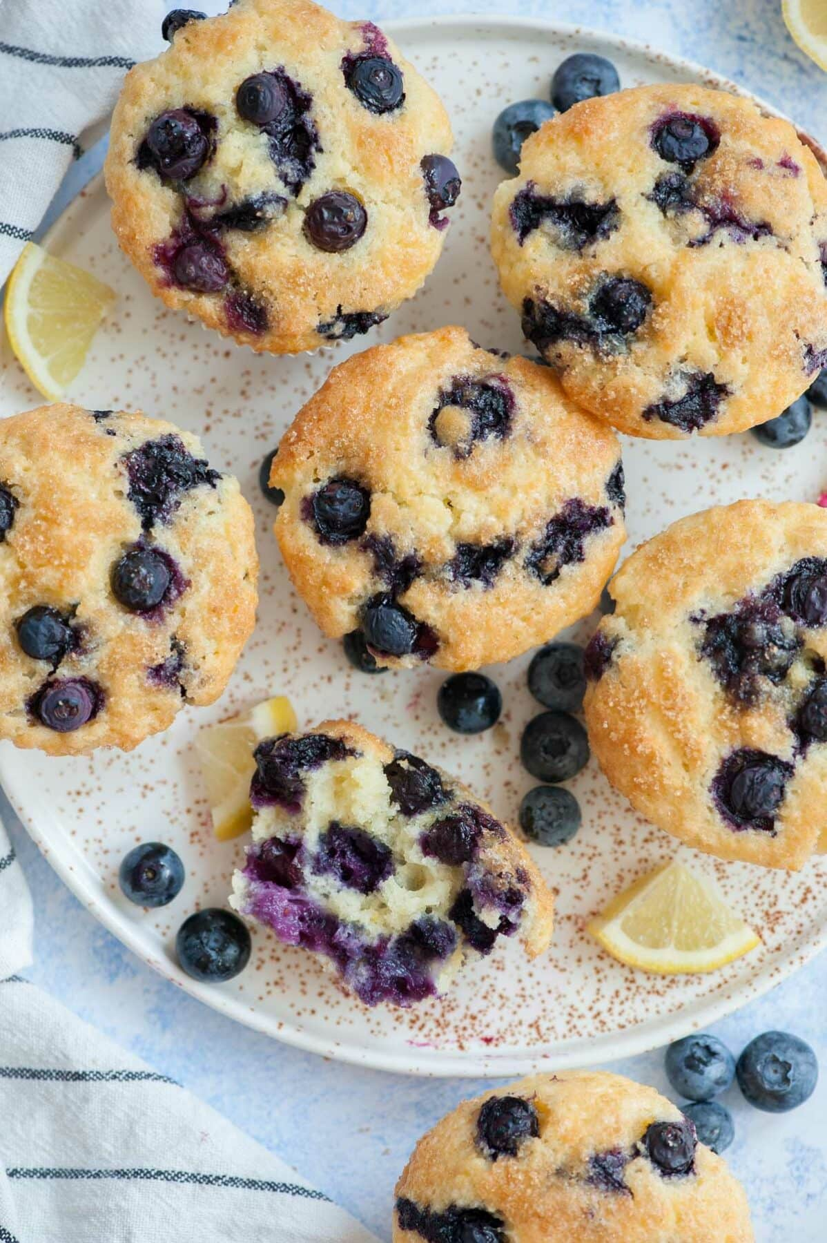 Overhead picture of blueberry yogurt muffins with one muffin cut in half.