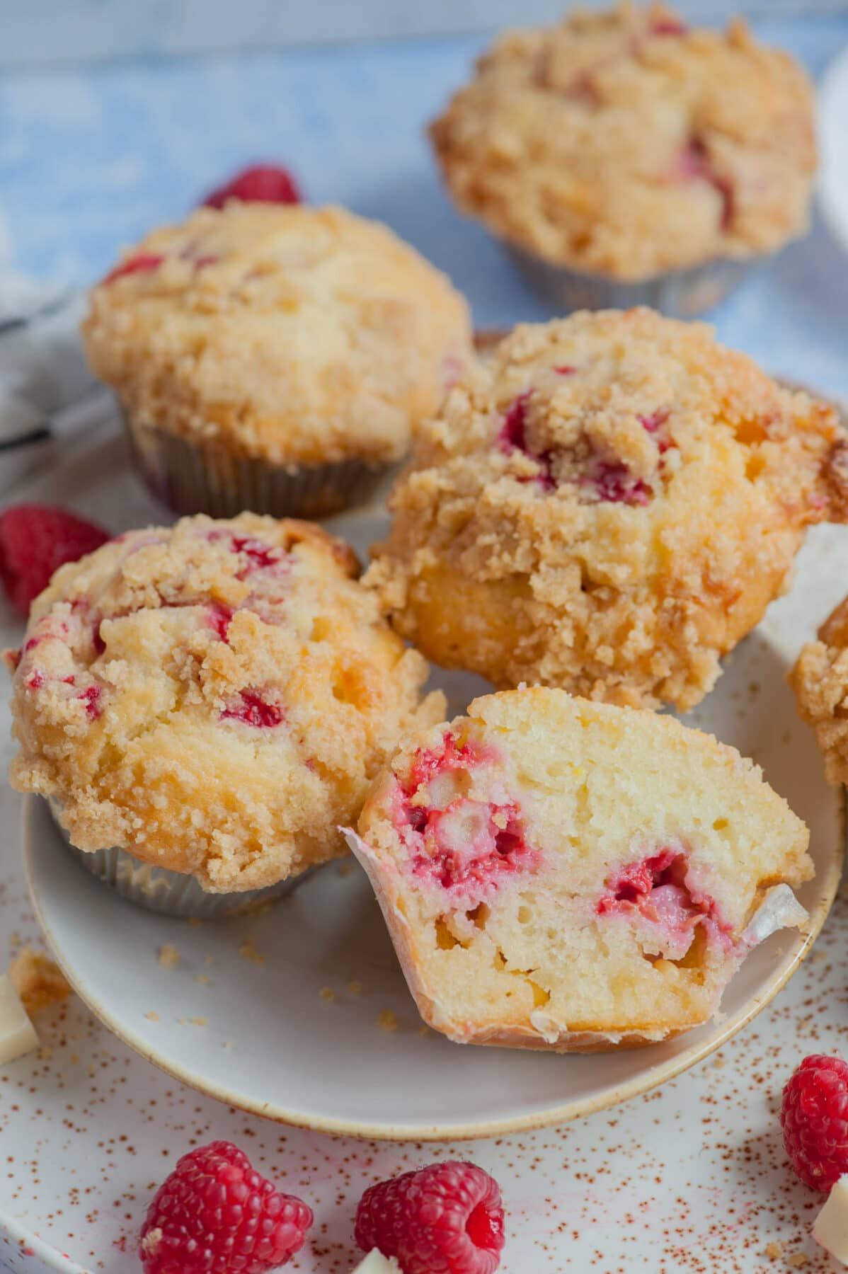 Raspberry muffins on a white plate. Raspberries and white chocolate chunks scattered around.