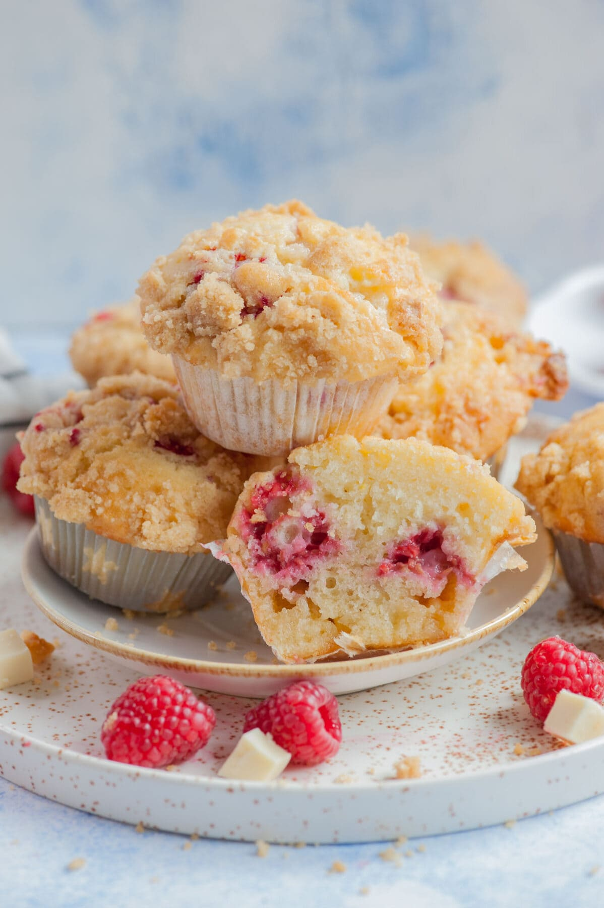 Raspberry muffins on a white plate. One muffin cut in half. Raspberries and white chocolate chunks scattered around.
