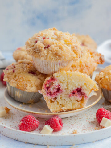 Raspberry muffins on a white plate. One muffin cut in half.