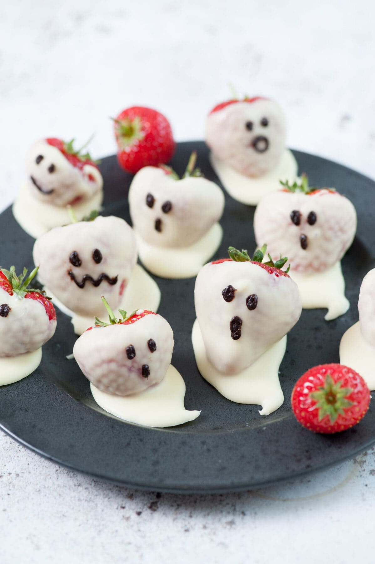 White chocolate covered strawberries (Strawberry ghosts) on a black plate.