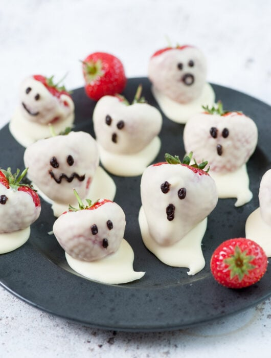 Strawberry ghosts on a black plate.