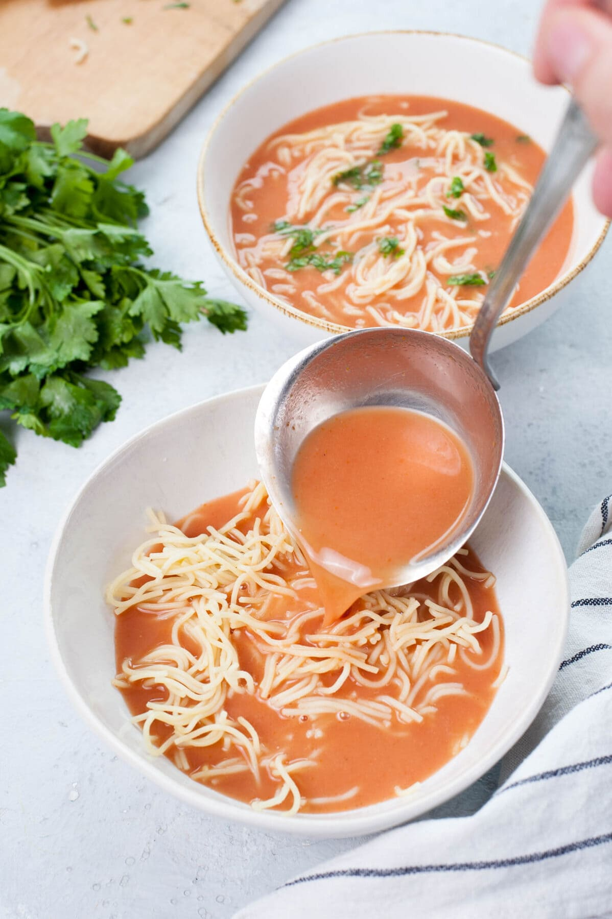 Tomato soup is being poured into a plate with cooked noodles.