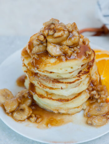 A stack of bananas foster pancakes on a white plate.