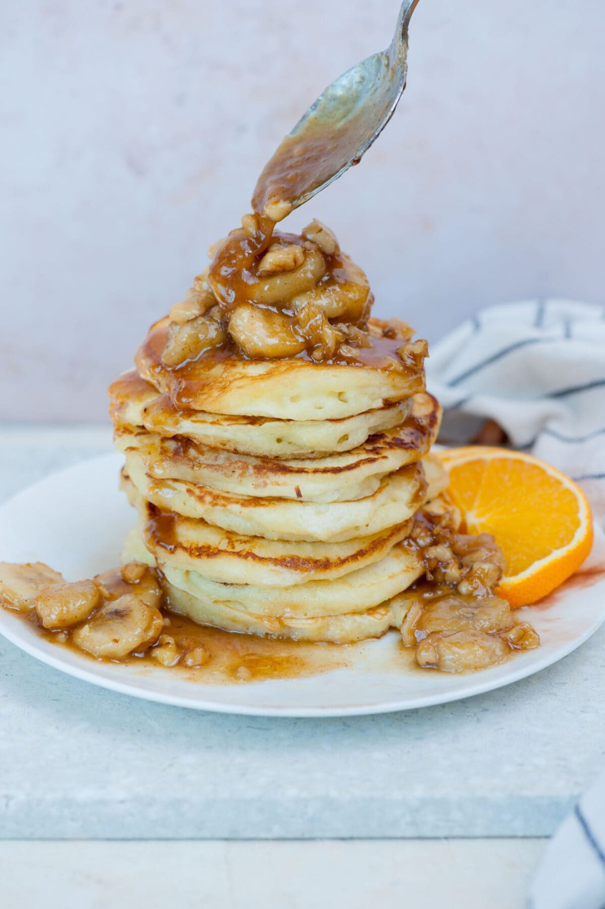 Bananas foster topping is being spooned over a stack of pancakes.