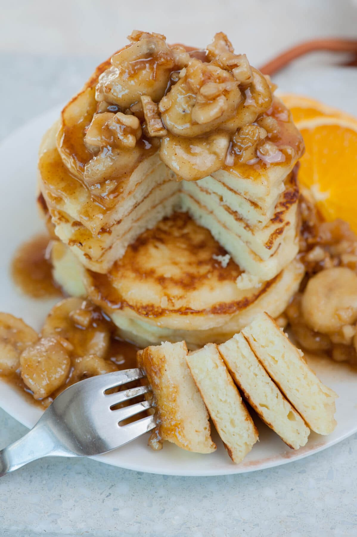 A stack of banana foster pancakes with a part cut of and stuck on a fork.