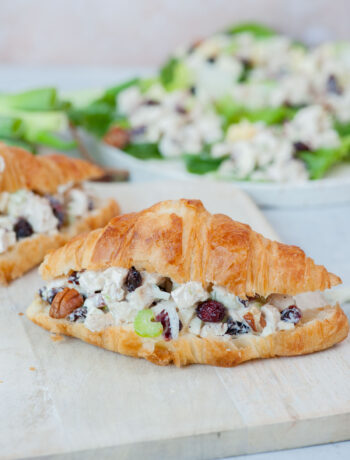 Cranberry chicken salad croissant sandwich on a white cutting board.