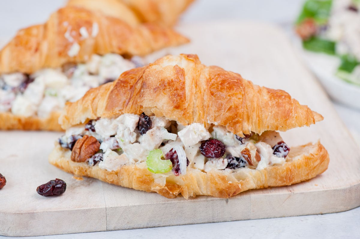 Croissant sandwich with cranberry chicken salad on a beige wooden board.