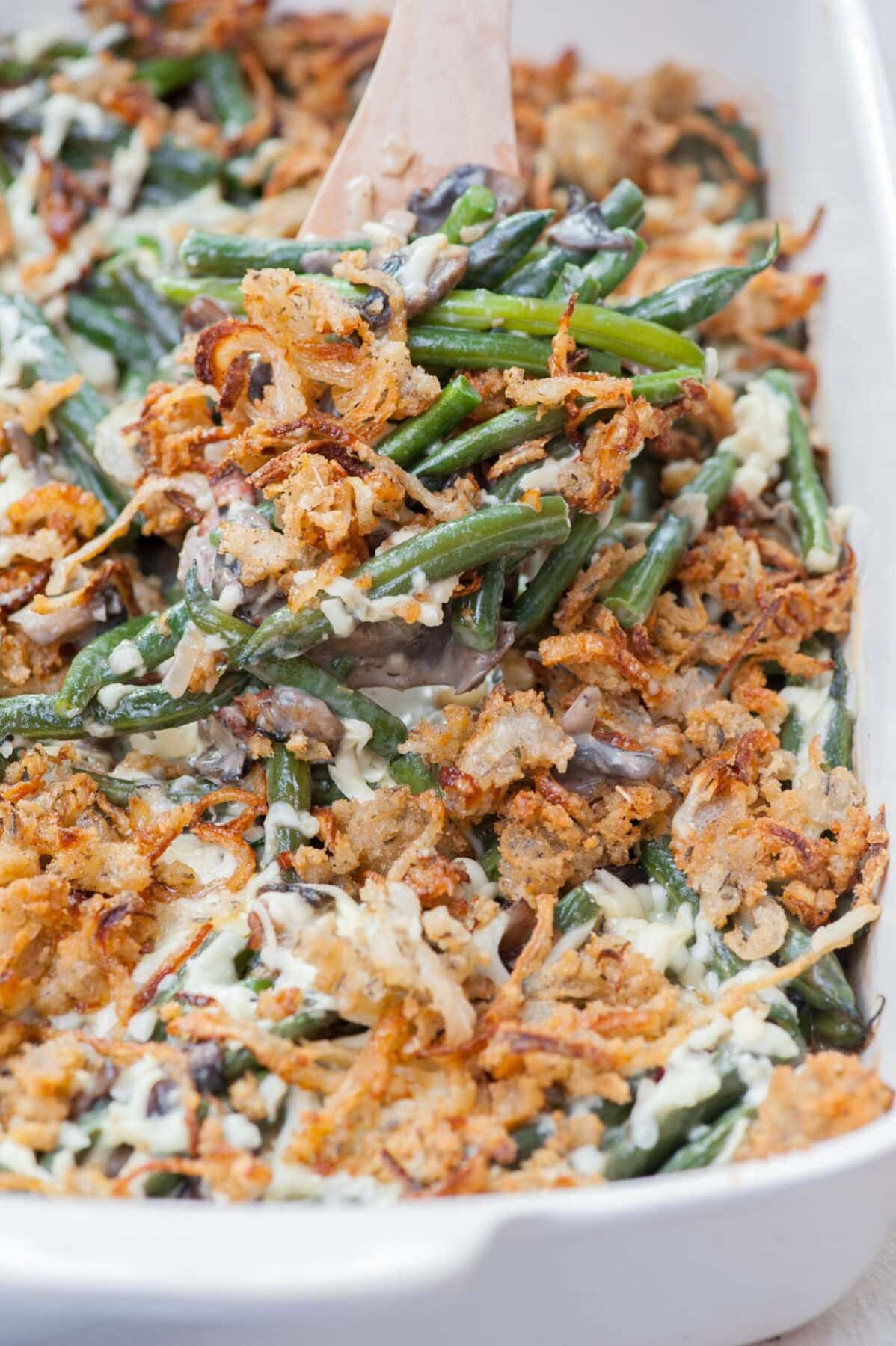 Green bean casserole in a white baking dish is being loaded on a wooden spatula.