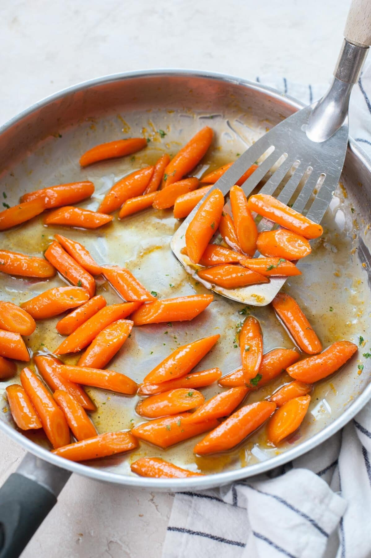 Honey glazed carrots are being scooped with a spatula from a frying pan.