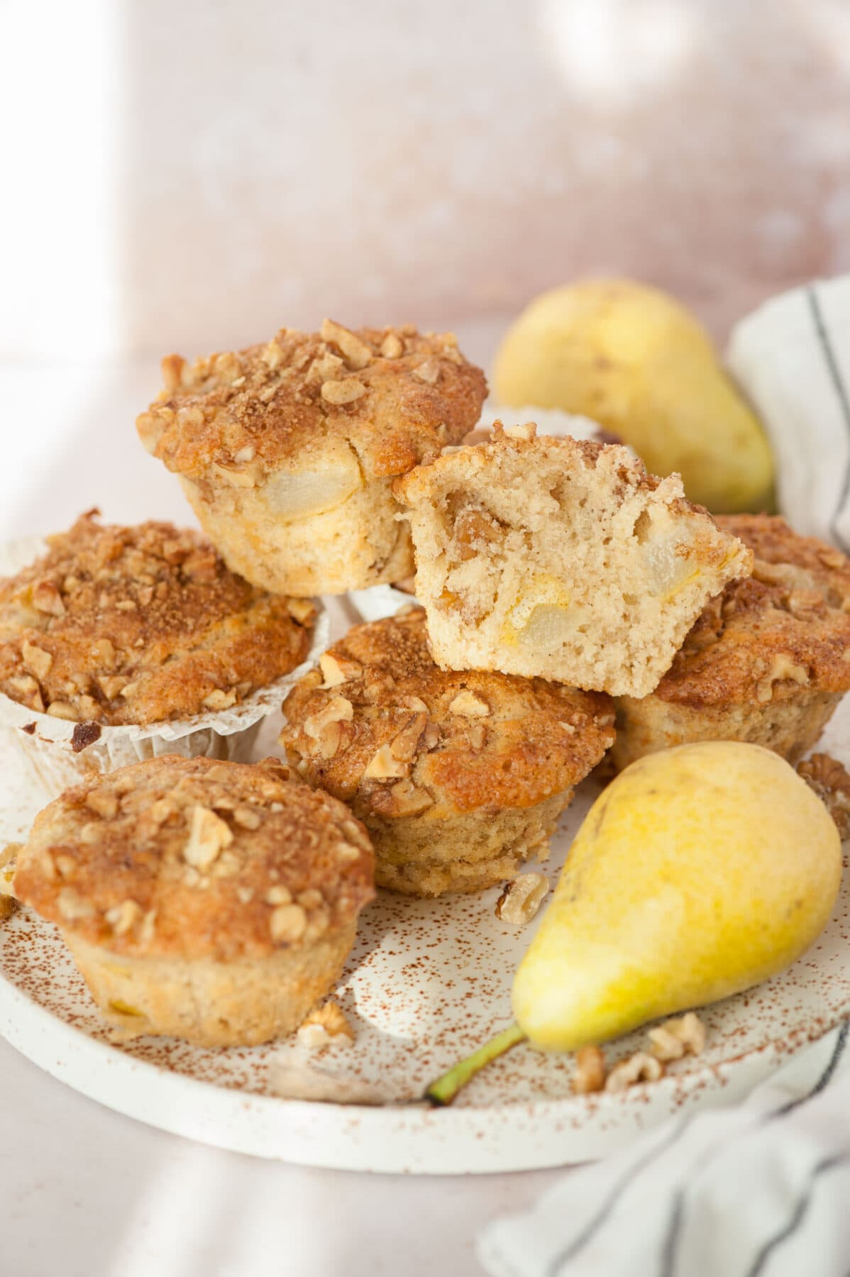 Pear muffins, pears, and walnuts on a white plate. One muffin cut in half.