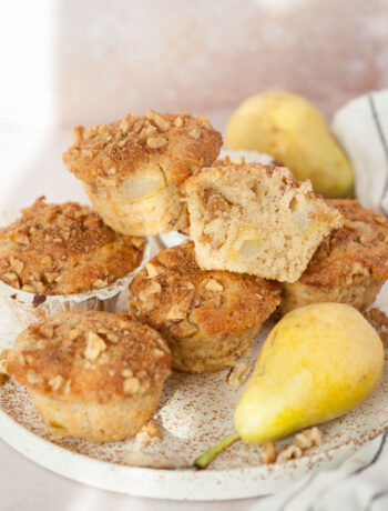 Pear muffins, walnuts, and pear on a white plate.