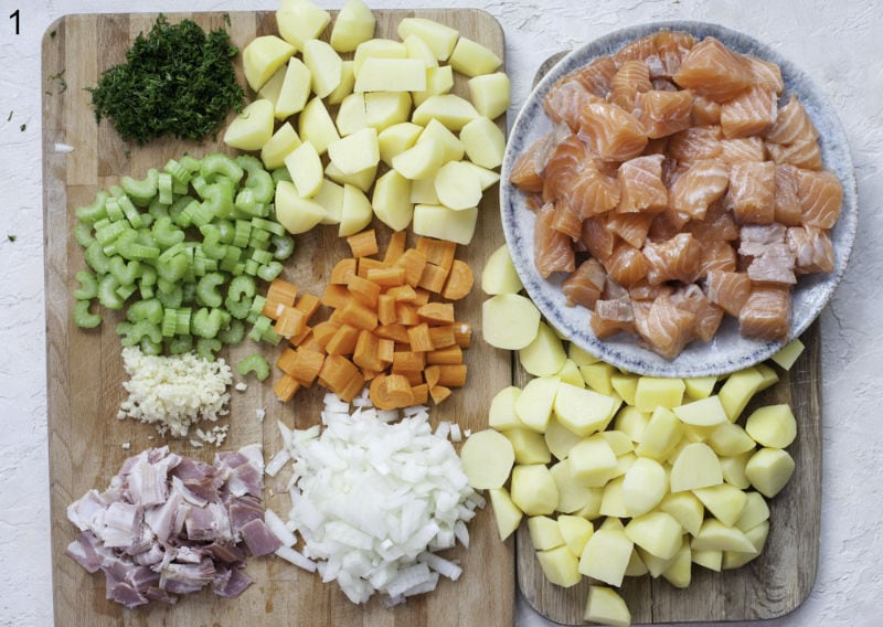 Chopped ingredients for salmon chowder on a chopping board.