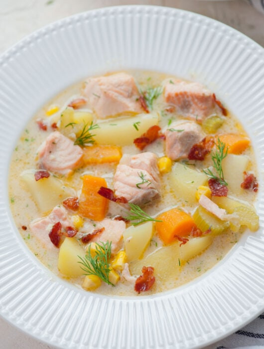 Salmon chowder in a white plate.