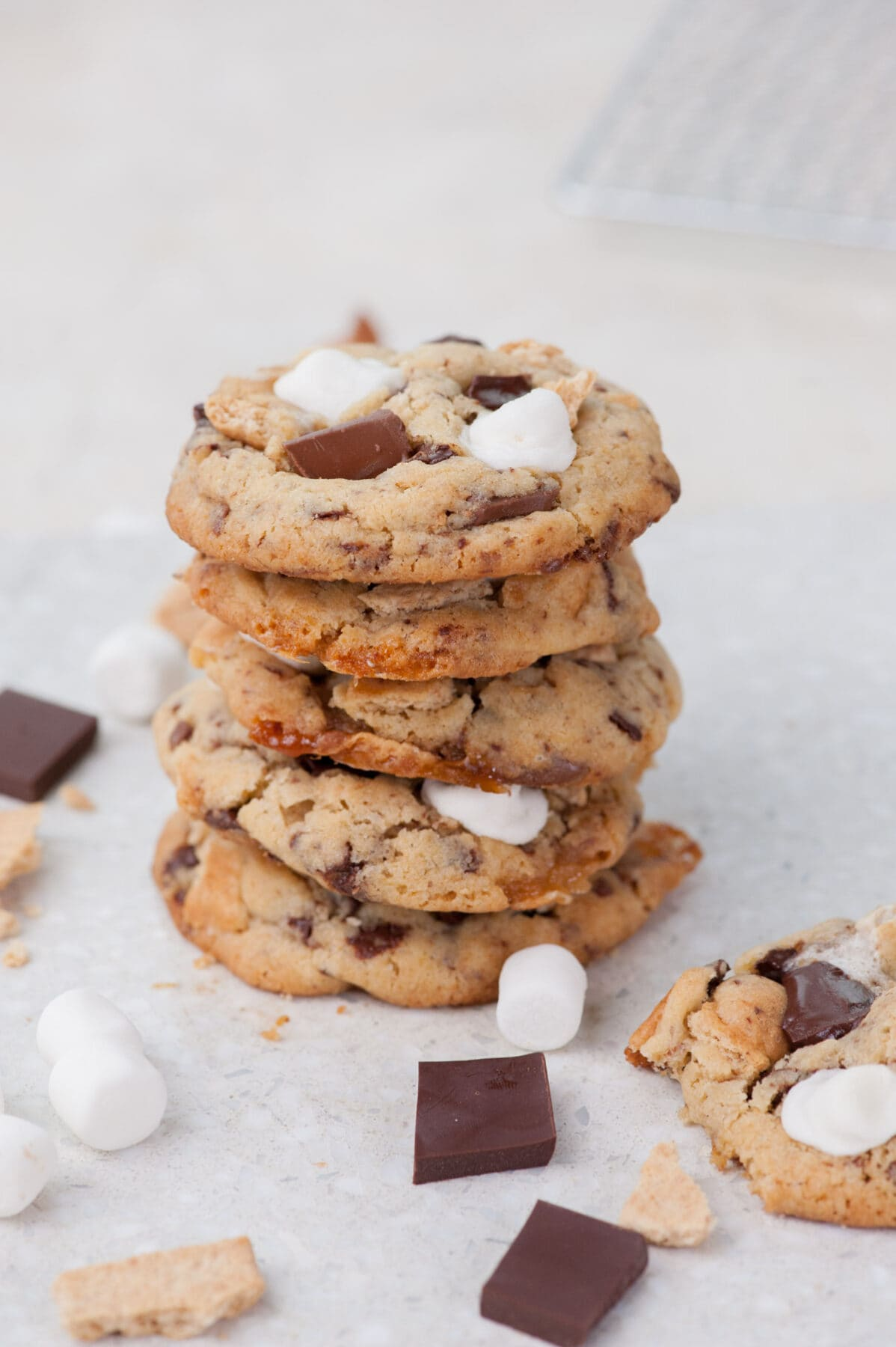 A stack of s'mores cookies on a grey background. Marshmallows and chocolate scattered around.