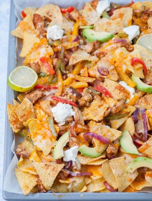 Chicken fajita nachos on a baking sheet.