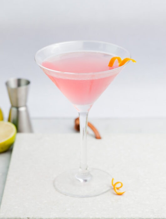 Cosmopolitan cocktail in a martini glass garnished with an orange twist.