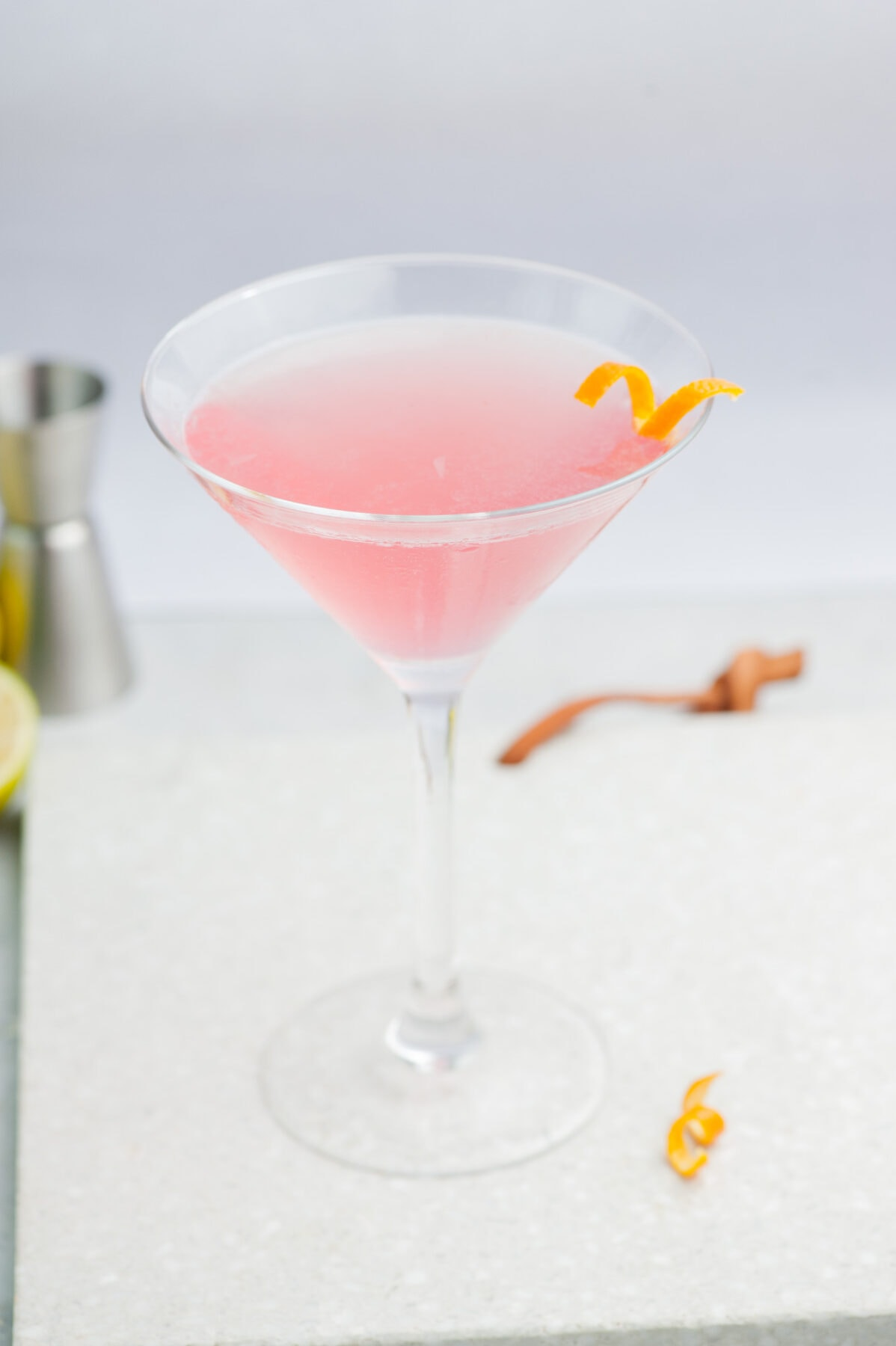 Cosmopolitan cocktail in a martini glass on a grey background, garnished with an orange twist.