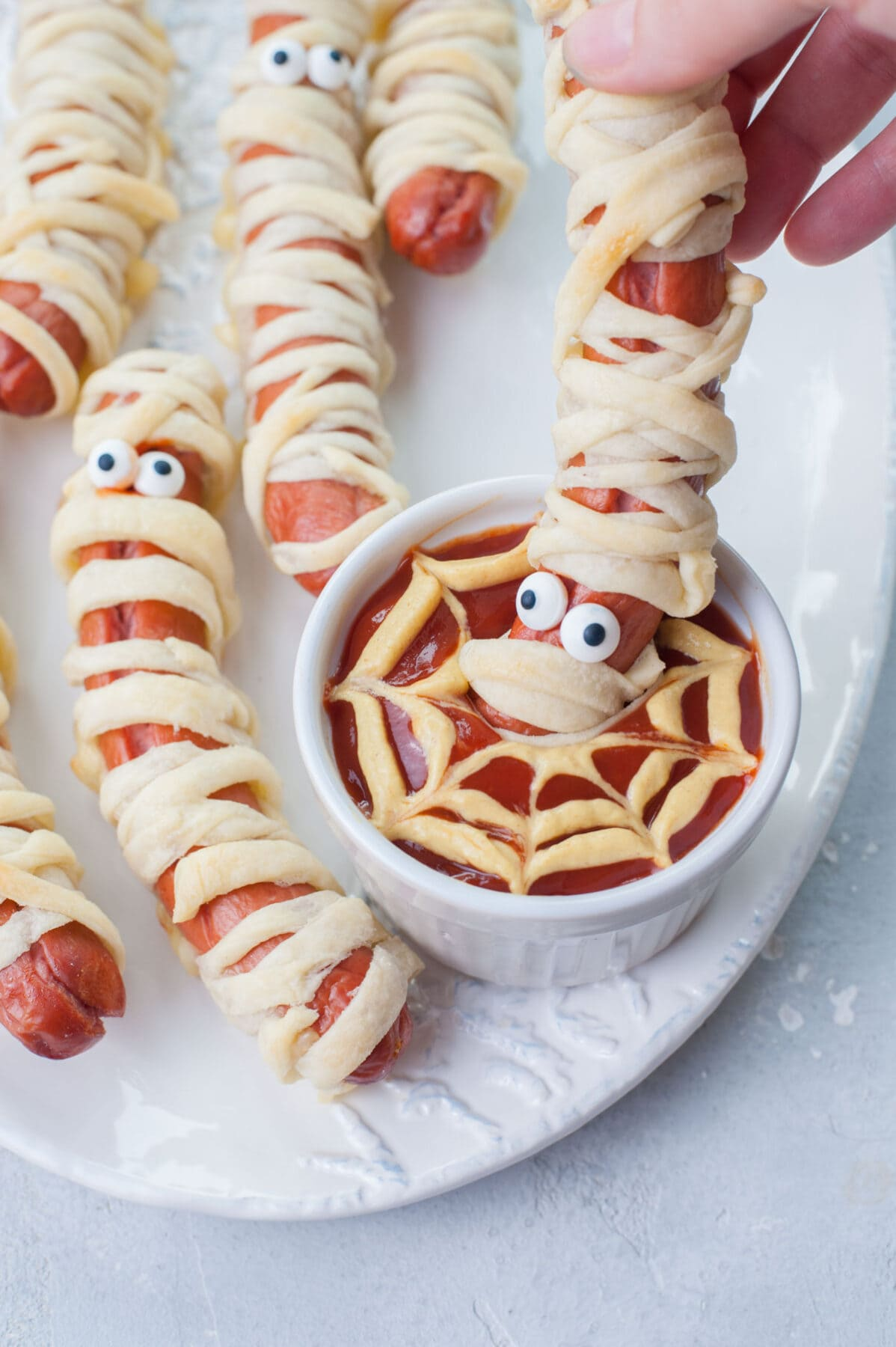 A mummy hot dog is being dipped in spider's web ketchup-mustard dip.