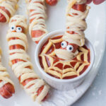 Mummy hot dogs are being dipped in ketchup.
