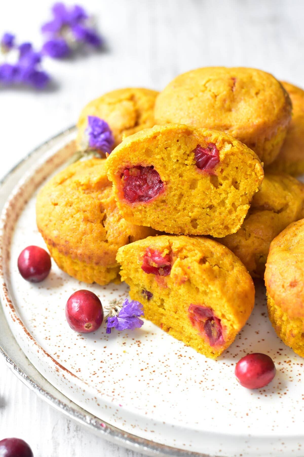 Pumpkin cranberry muffins on a white plate. Two muffins are cut in half.