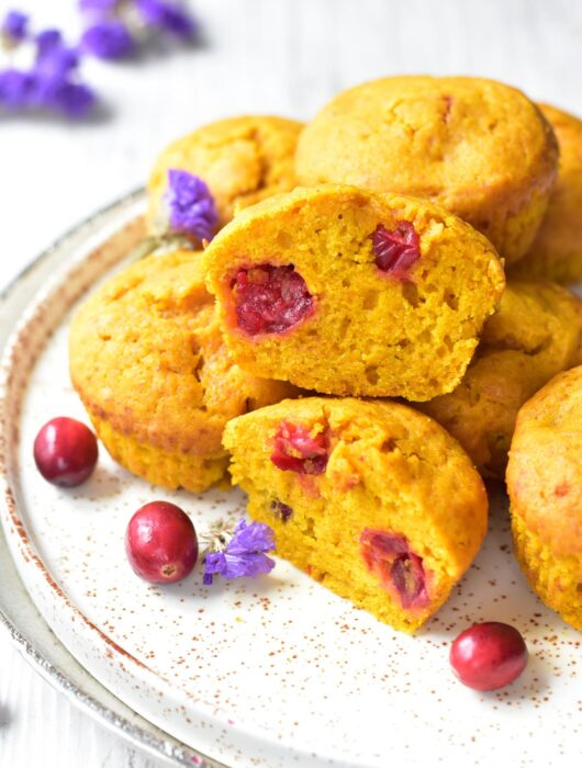 Pumpkin cranberry muffins on a white plate. Two muffins cut in half.