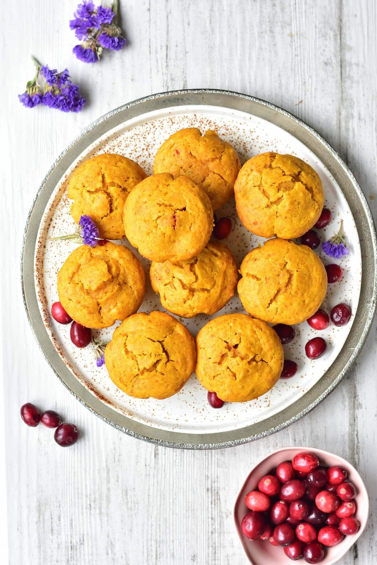 Overhead picture of pumpkin cranberry muffins on a white plate.