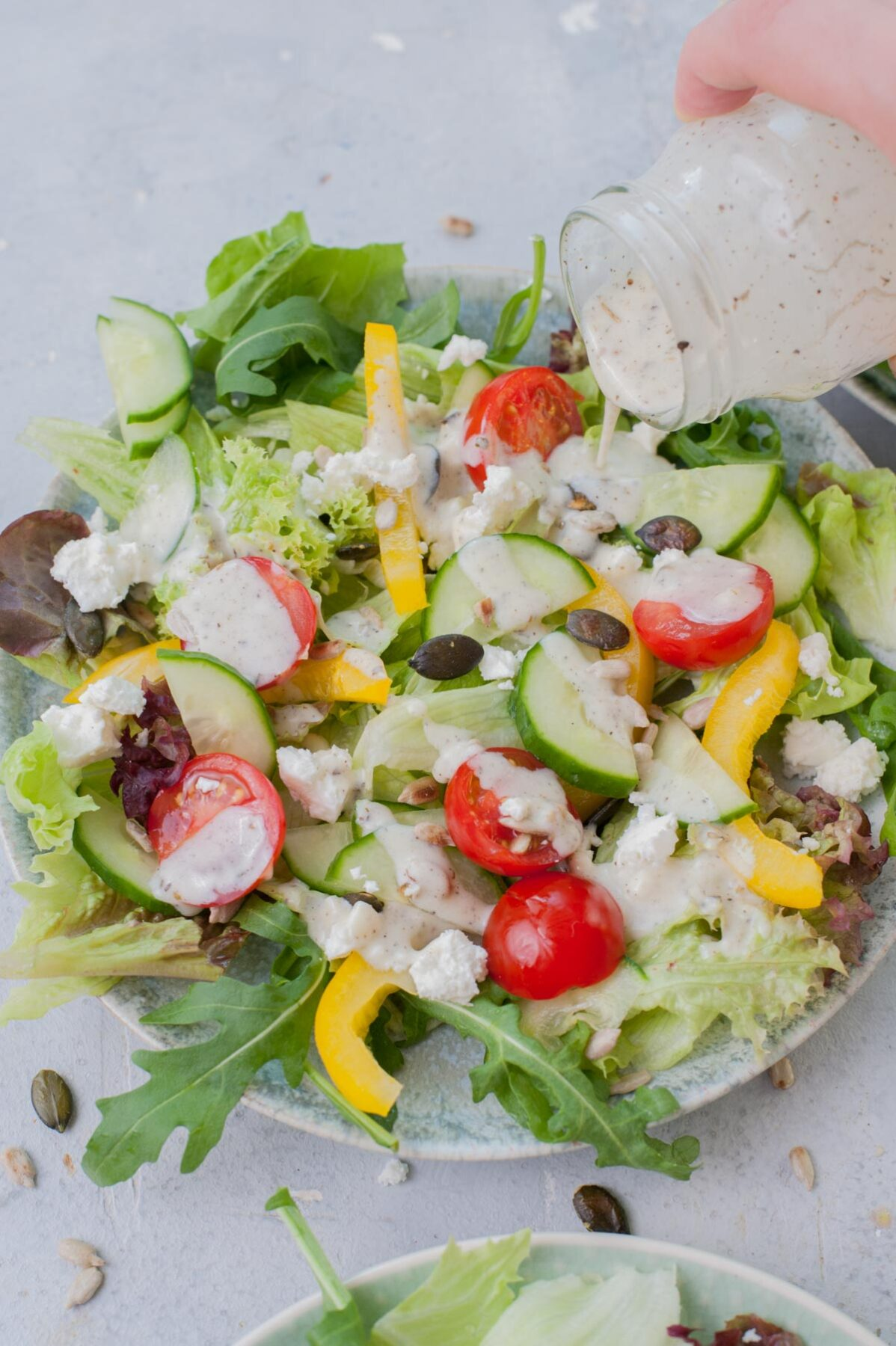 Yogurt dressing is being poured over lettuce and veggies on a green plate.