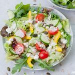 Salad with yogurt dressing on a green plate.