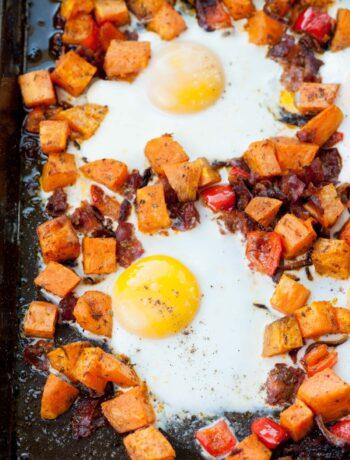 Sweet potato breakfast hash with eggs on a black baking sheet.